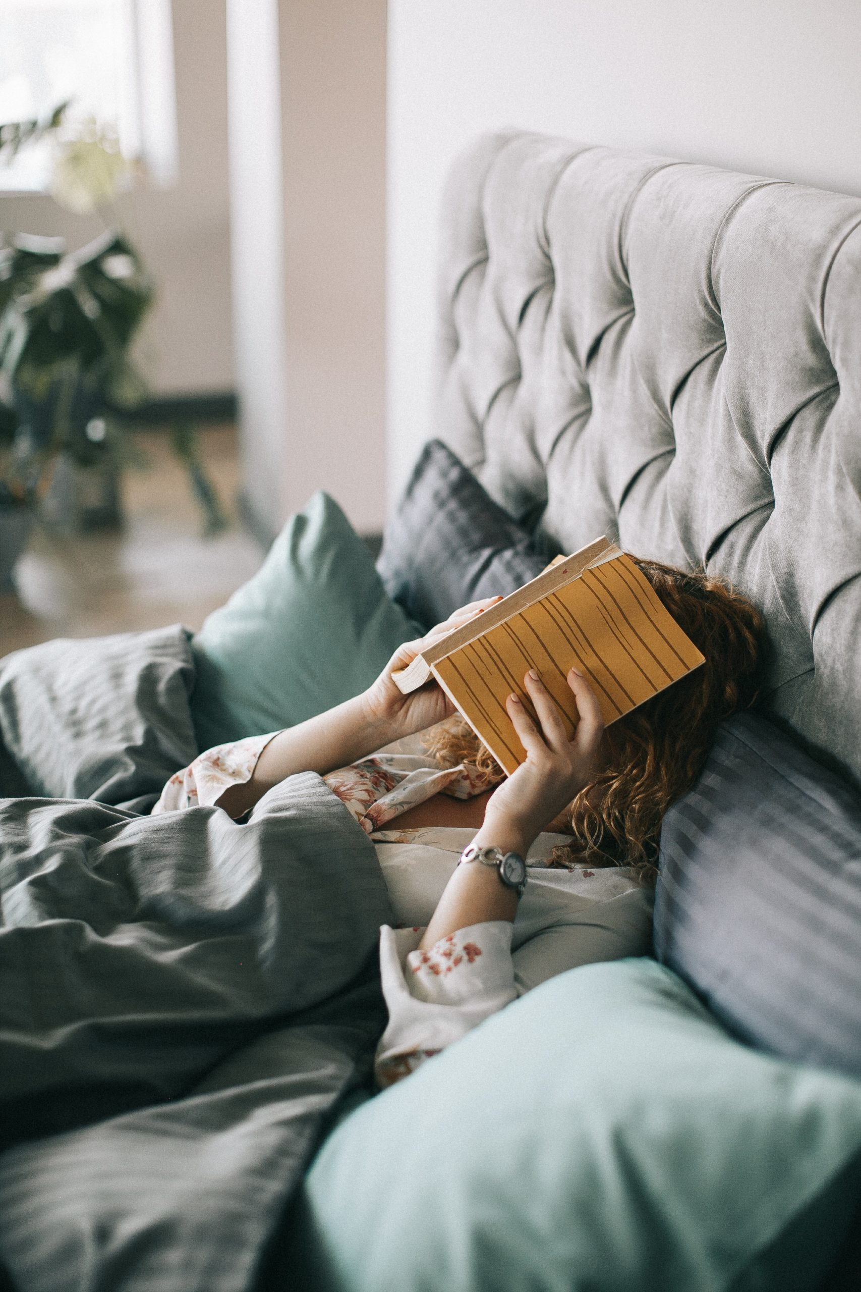 woman-covering-face-with-book-on-bed-1524232